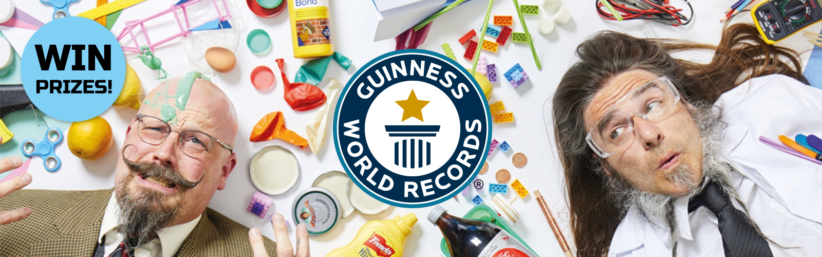 guinness world records logo with win prices badge and two men who look like teachers lying on a surface covered in balloons, lego mustard and other products