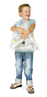 young boy smiling holding a bag of recycling packages contained in a plastic bag