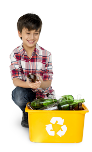 young boy crouching down piling empty glass bottles into a yellow recycling container