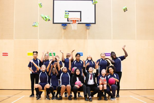 girls from george mitchell school throwing always end period poverty pads in the air in sports gym