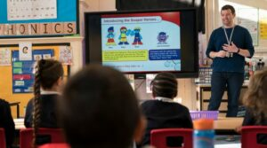 Male teacher standing next to a large screen at the front of a class of primary learners giving the Soaper Heroes PowerPoint presentation