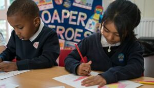 Two primary children in a classroom completing worksheets with Soaper Heroes wall display behind